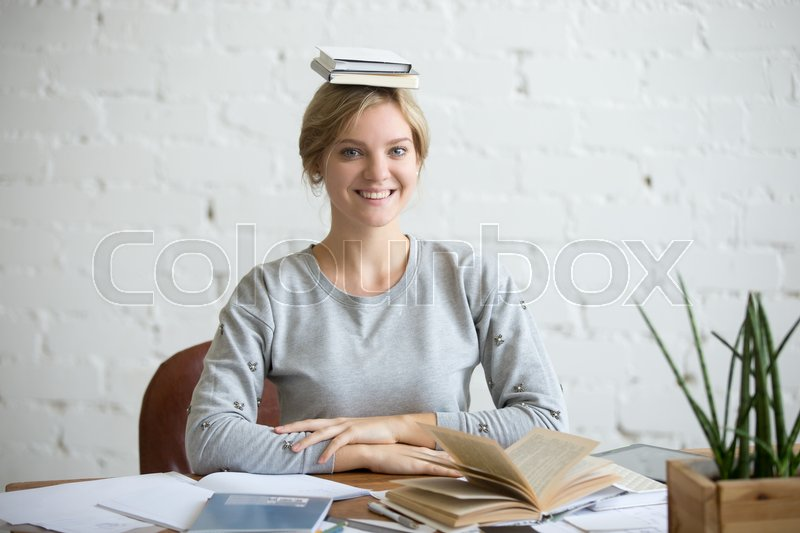 Stock image of 'Portrait of a young smiling woman at the desk with books on her head, sitting straight, looking at the camera. Education concept photo'