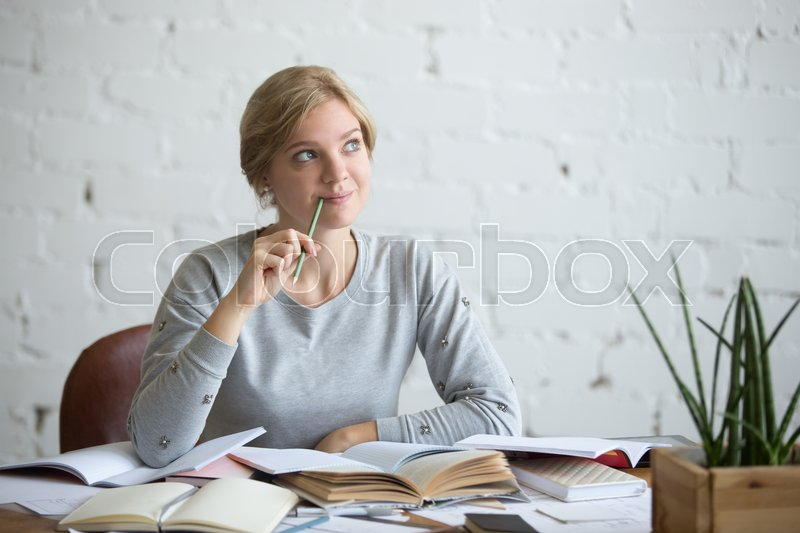 Stock image of 'Portrait of a dreaming student woman sitting at the desk, head in the clouds, lifestyle. Education concept photo'
