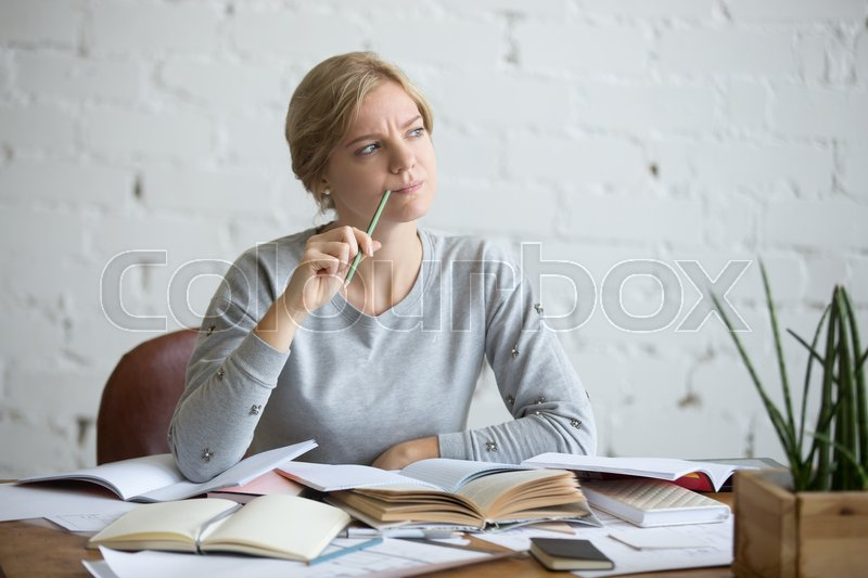 Stock image of 'Portrait of a student woman sitting at the desk, frowned, looking aside lifestyle. Education concept photo'