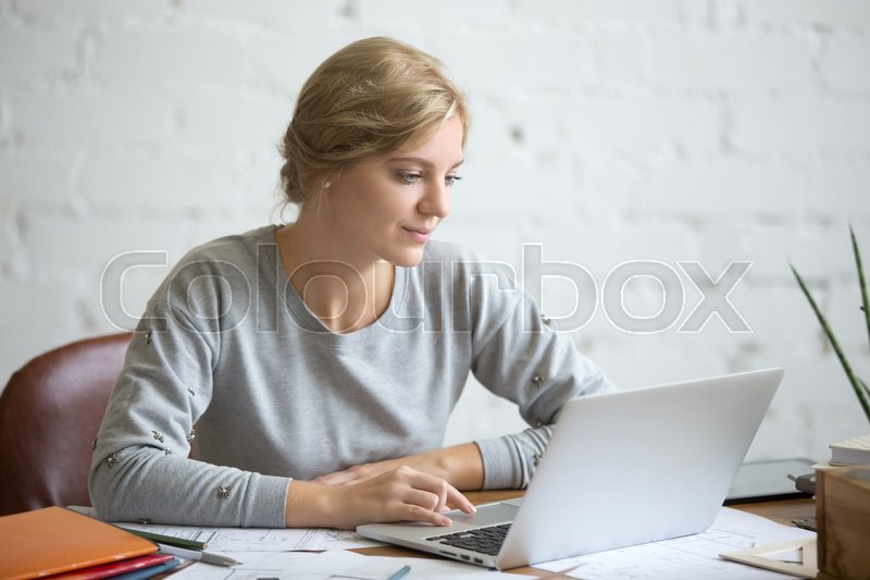 Stock image of 'Portrait of a young attractive student girl sitting at the desk working with a laptop, education concept photo, lifestyle'
