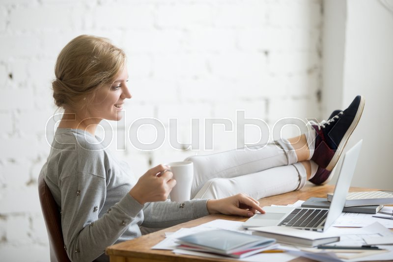 Stock image of 'Profile portrait of a smiling student girl working with a laptop, her legs on the desk, mug in her hand. Education concept photo, lifestyle'