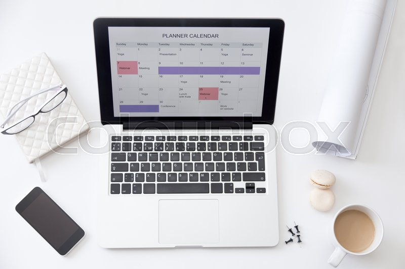 Stock image of 'High angle view image of a working desk. Open laptop on the desk with a planner calendar on the screen. Business concept photo, close up'