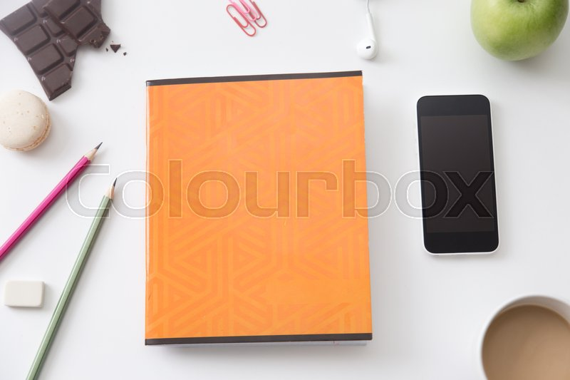 Stock image of 'Top view of a white office desk with an orange copybook in the centre, flat lay. Education concept photo, close up, copy space'