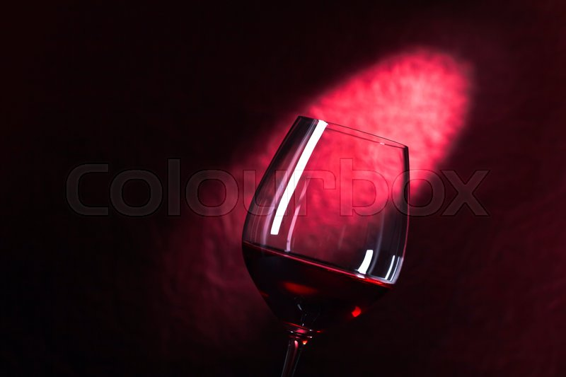 Stock image of 'glass of red wine on a dark red background'