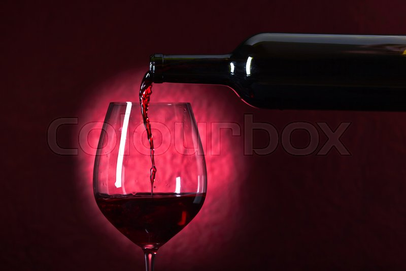 Stock image of 'Bottle and glass of red wine on a dark red background'