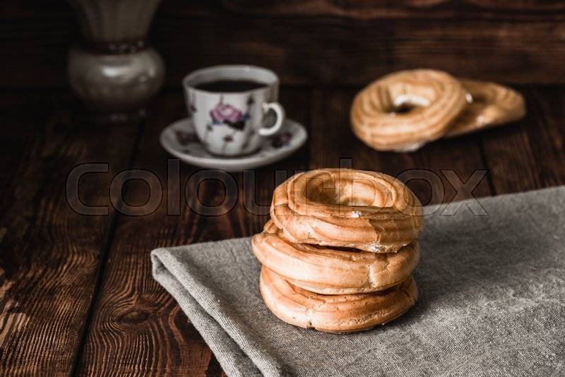 Stock image of 'Round eclairs stacked on the table. Cup with the Beverage and few eclairs on background.'