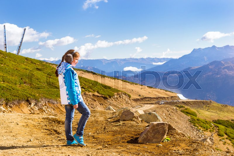 Stock image of 'Girl with pigtail, dressed in jacket and warm fluffy headphones, admires of autumn mountain landscape, views of hills and peaks of Caucasus mountains. Krasnaya Polyana Alpine ski resort. Sochi, Russia'