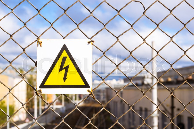 Stock image of 'Yellow warning sign with high voltage symbol hanging on the protective metal grid. Protection on high voltage train wires. Transport infrastructure of Russian Railways, Saint-Petersburg'