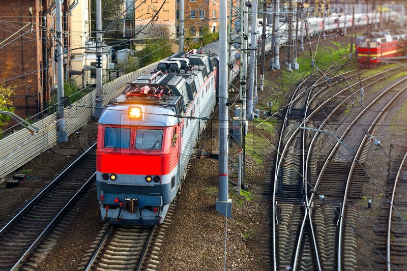 Stock image of 'Electric locomotive pulling high-speed train on rails. Technical railway station - operational locomotive depot. Transport infrastructure of Russian Railways, Saint-Petersburg'
