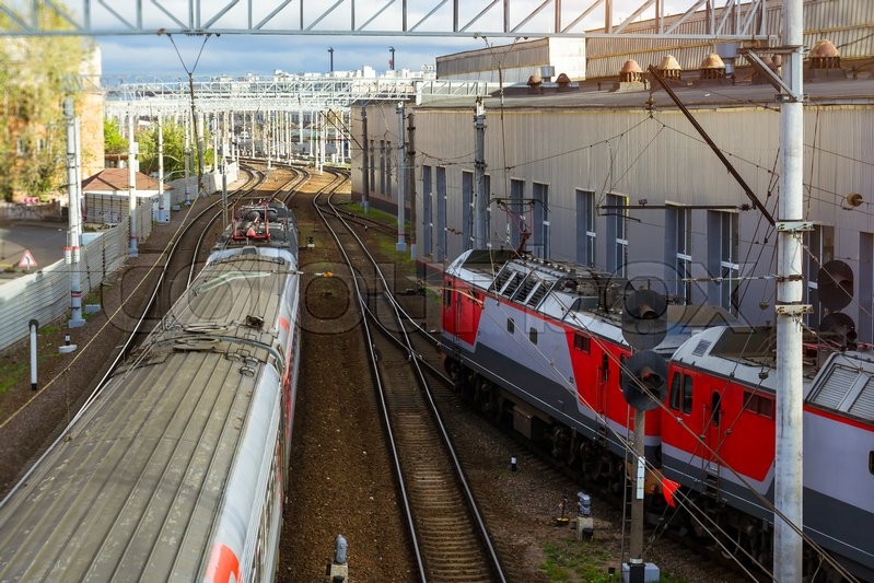 Editorial image of 'Electric locomotive pulling high-speed train on rails. Technical railway station - operational locomotive depot. Transport infrastructure of Russian Railways, Saint-Petersburg'