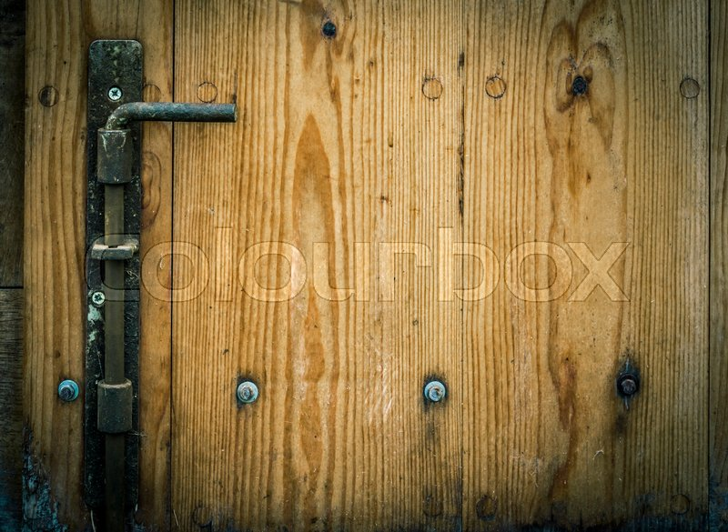 Stock image of 'Latch and wooden planks, part of an aged door from a german warehouse, with copy space on the right side for your text.'