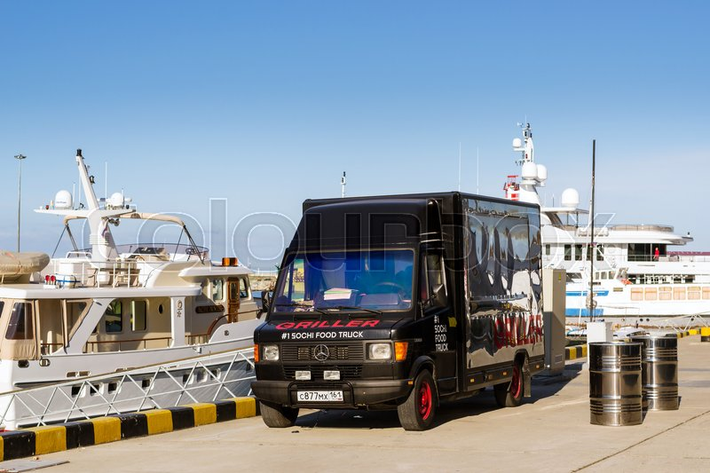 Editorial image of 'Sochi, Russia - November 1, 2015: Parked food truck - black truck-refrigerator Mercedes brought two barrels of beer at pier in Sochi seaport. Marine station complex Port. Krasnodarskiy kray, Russia'