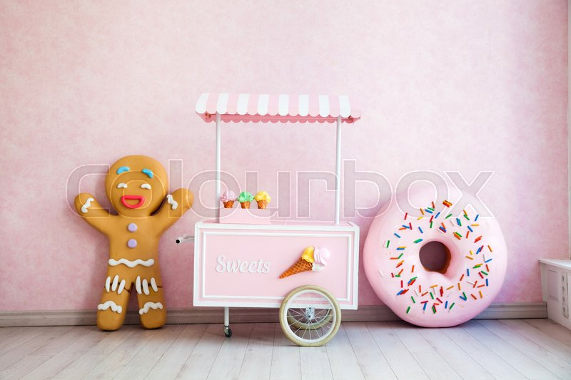 Stock image of 'Gingerbread man, donut and ice-cream handcart in funny room interior'