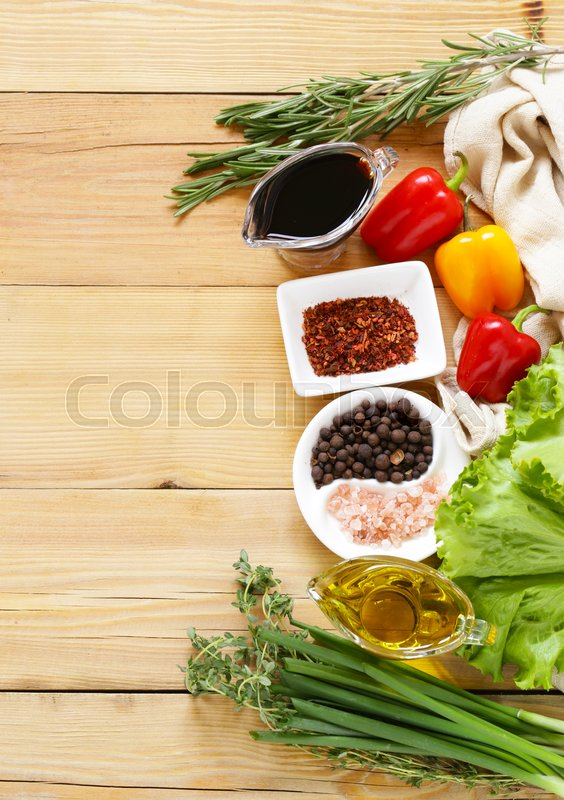 Stock image of 'Herbs and spices, vegetables and sauces on wooden background'