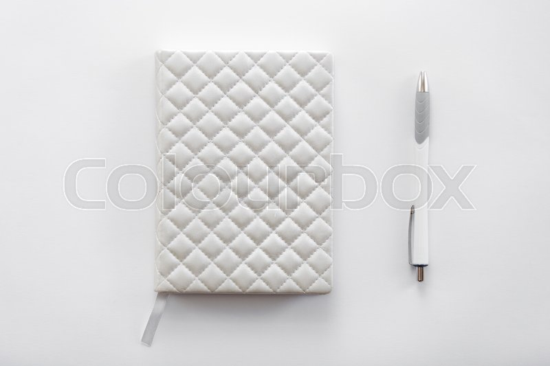 Stock image of 'White office desk with a notebook and pen on it. Top view with copy space, business concept photo'
