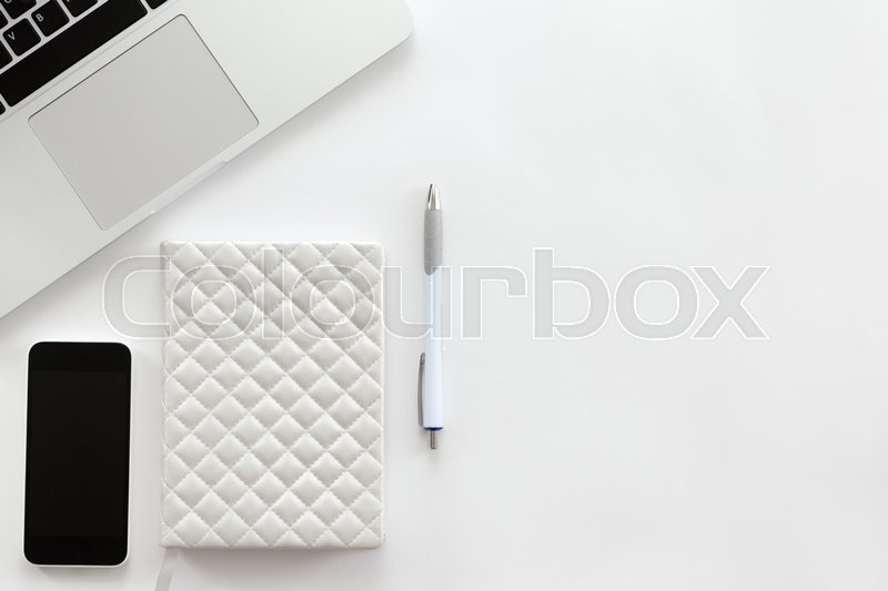 Stock image of 'White office desk with a part of laptop, mobile phone, and pen on it. Top view with copy space, right side'
