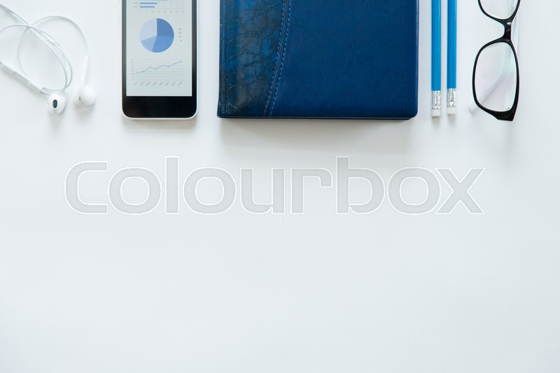 Stock image of 'White office desk with glasses, mobile phone, earphones and pencils on it. Male office supply. Top view with copy space'