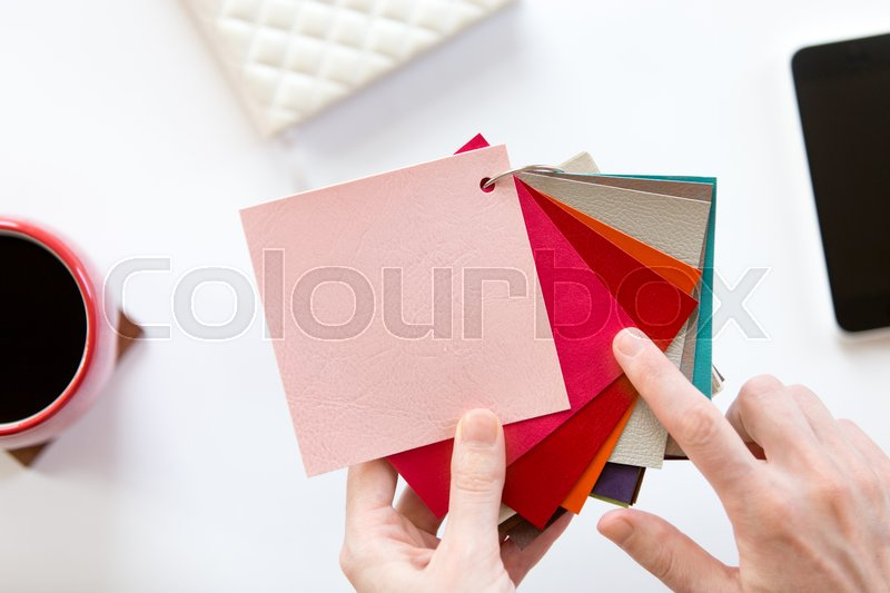 Stock image of 'Female hands choosing a color fabric pattern above a white office desk. Top view with copy space, design concept photo'