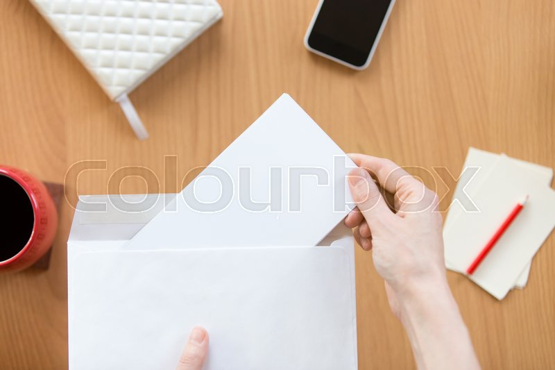 Stock image of 'Female hands holding an envelope with a blank paper sheet over the office desk. Top view with copy space'