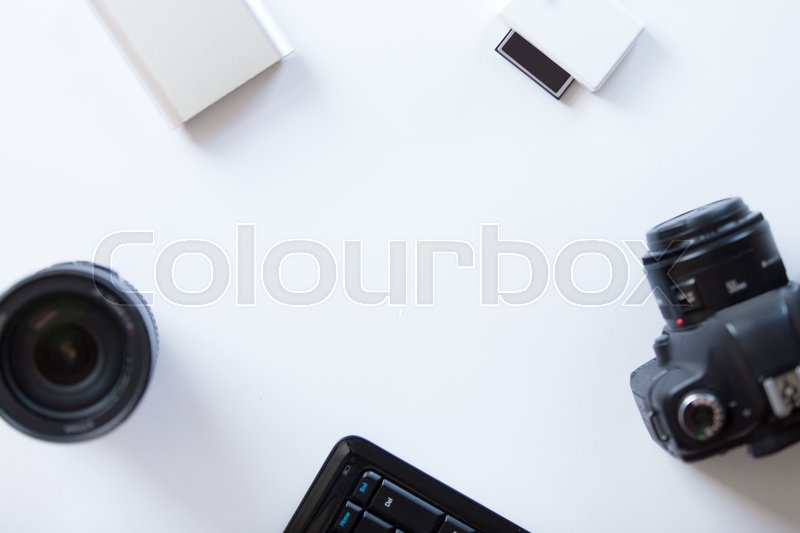 Stock image of 'White desk with a professional camera and accessoires on it. Top view, copy space'