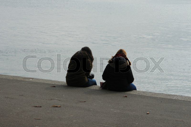 Stock image of 'The two schoolgirls discuter their problems at the lake in the city Lucerne in Switzerland in autumn.'