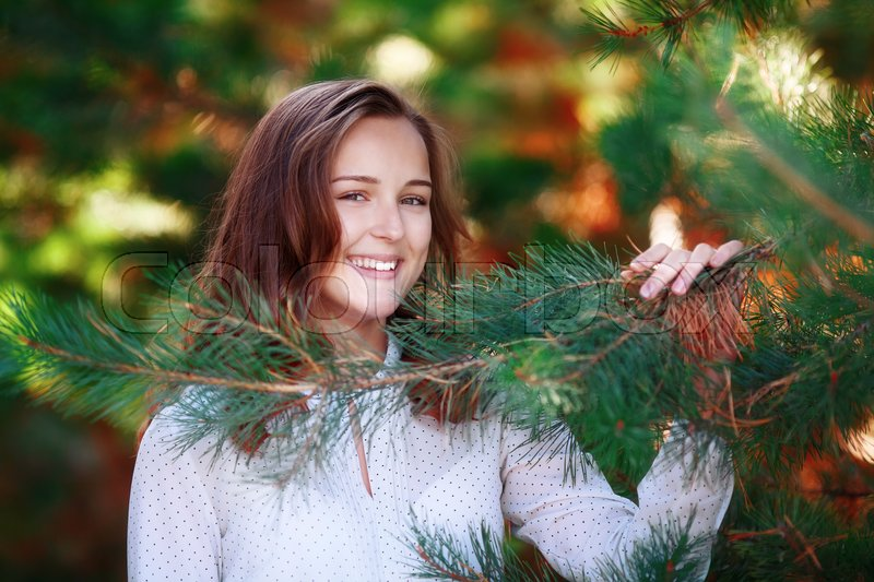 Stock image of 'Portrait of smiling pretty girl in green spruce branches, autumn park'