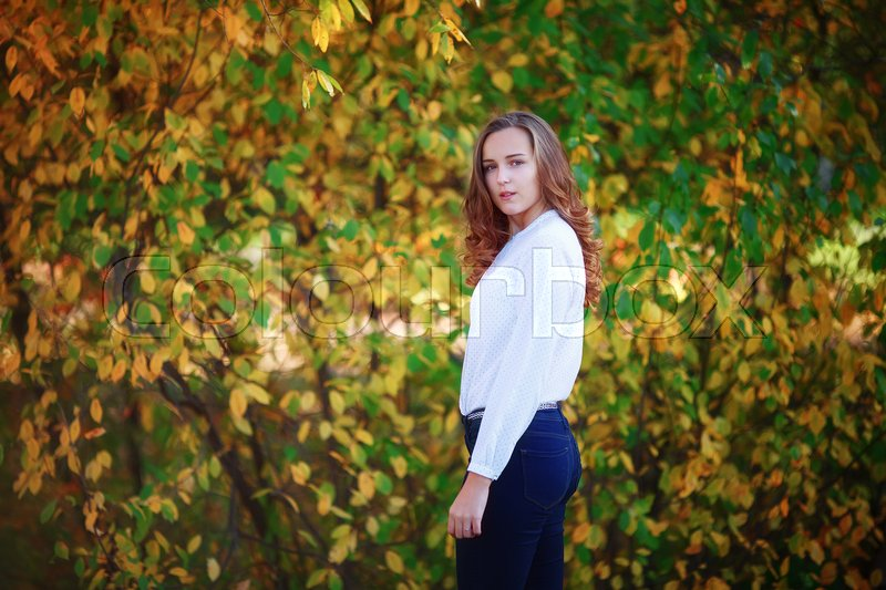 Stock image of 'Young beautiful woman. Pretty girl in bright colorful autumn park looking back'