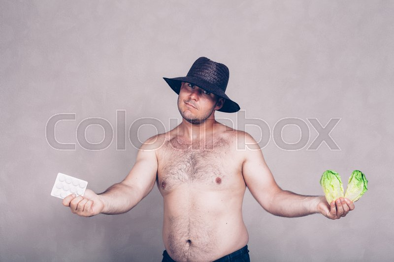 Stock image of 'Naked corpulent man in hat giving pharmaceutical products and lettuce.'