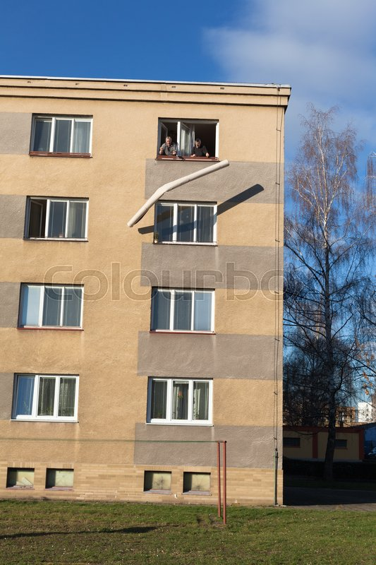 Stock image of 'Two seniors throwing rolled carpet out of a window from the top floor of a building.'