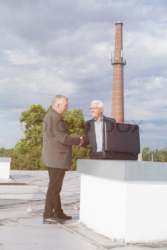 Stock image of 'Two senior businessmen with briefcase handshaking and making a business deal outdoors on the roof of a building.'