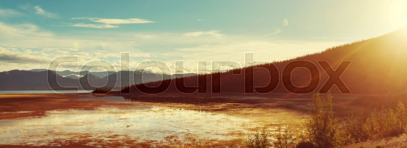 Stock image of 'Serene scene by the mountain lake in Canada with reflection of the rocks in the calm water.'