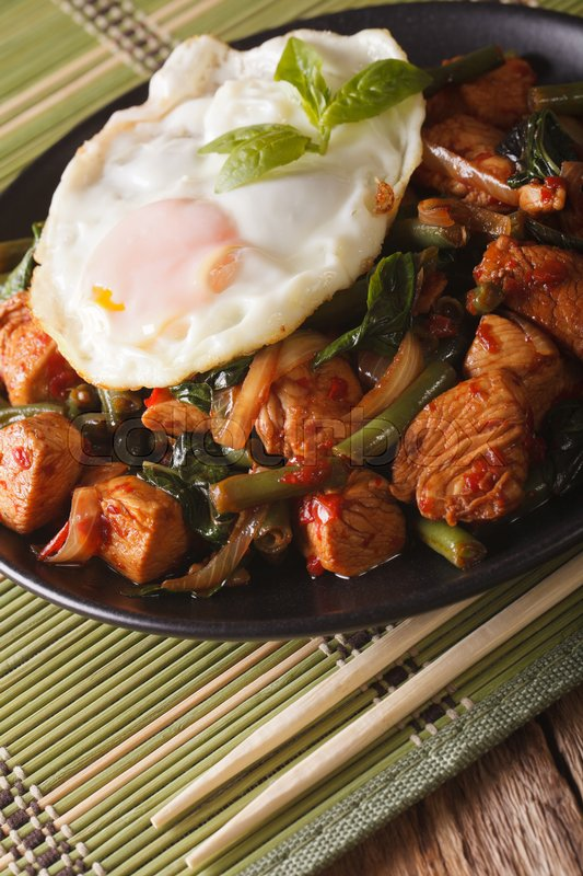 Stock image of 'Thai Gai Pad Krapow chicken with basil, green beans and a fried egg on a plate close-up vertical\'