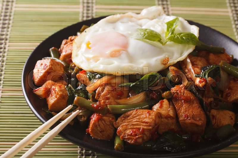 Stock image of 'Thai Gai Pad Krapow chicken with basil and egg close-up on a plate. horizontal\'