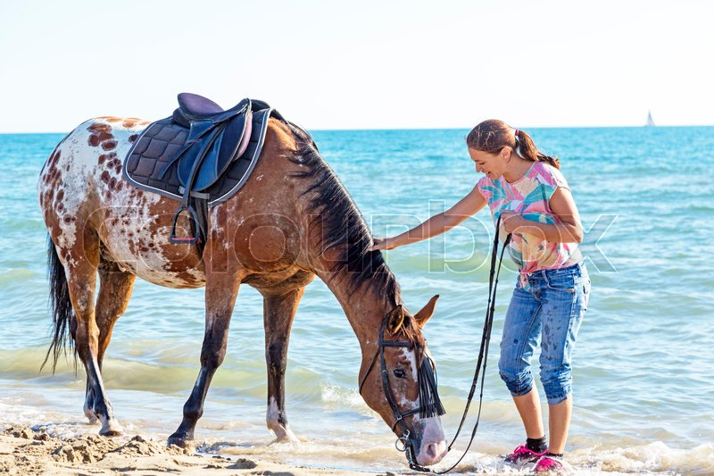 Stock image of 'woman and appaloosa horse walking on the beach'