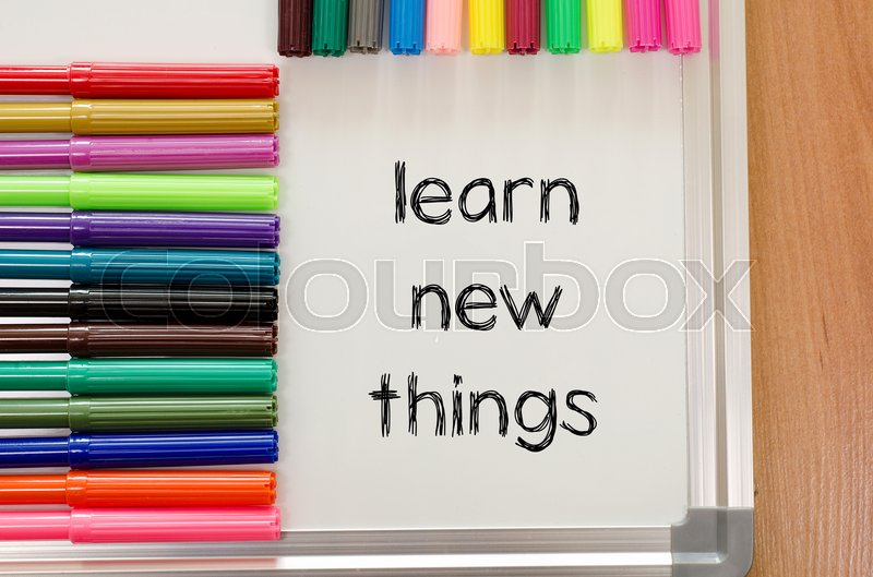 Stock image of 'Felt-tip pen and whiteboard on a wooden background and learn new things text concept'