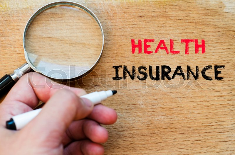 Stock image of 'Human hand over wooden background and health insurance text concept'