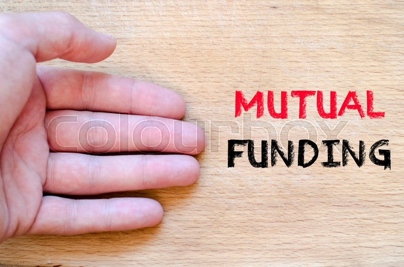 Stock image of 'Human hand over wooden background and mutual funding text concept'