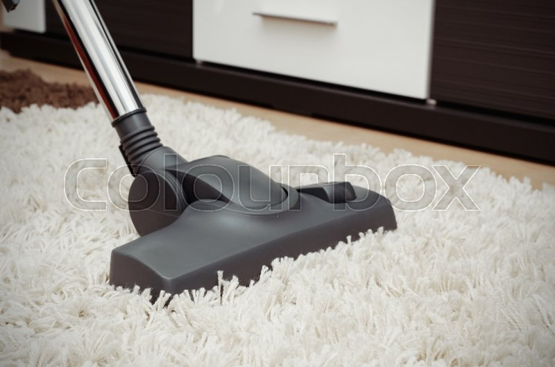 Stock image of 'Vacuum cleaner cleans the white shaggy carpet. Close up view'