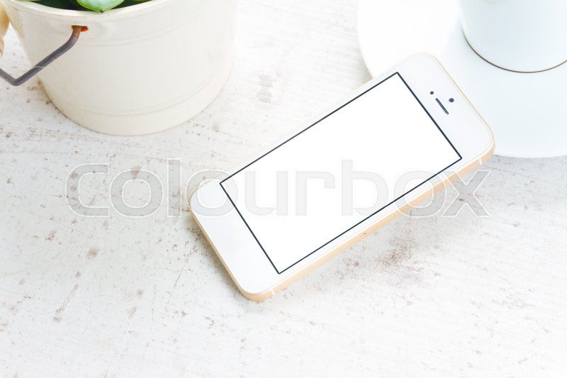 Stock image of 'Mock up styled flat lay white hight key scene with white phone, copy space on blank screen'
