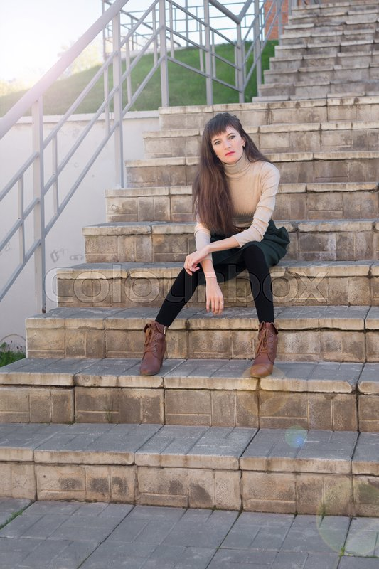 Stock image of 'Slim brunette girl with long hair in a green skirt and beige turtleneck sitting on the stone steps and looking into the camera'