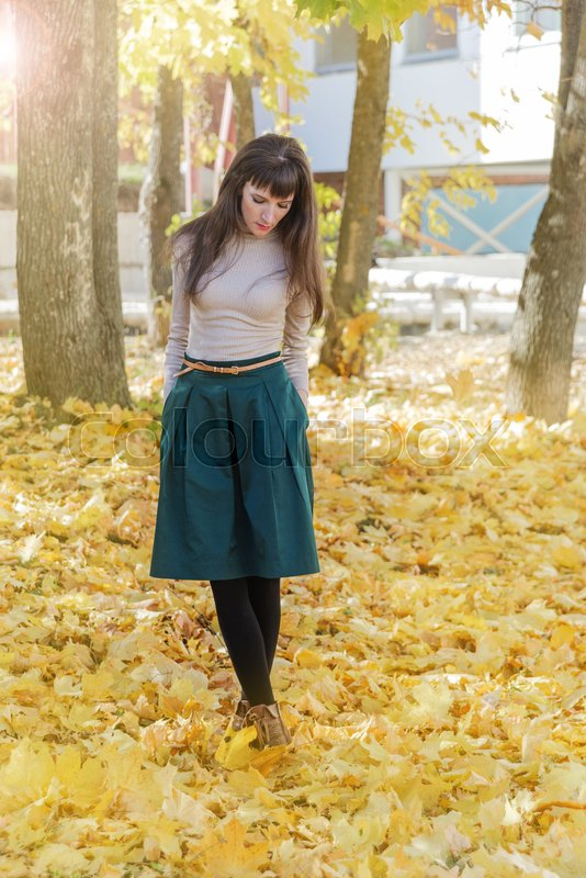 Stock image of 'Slim brunette girl with long hair in a green skirt and beige turtleneck in autumn park'