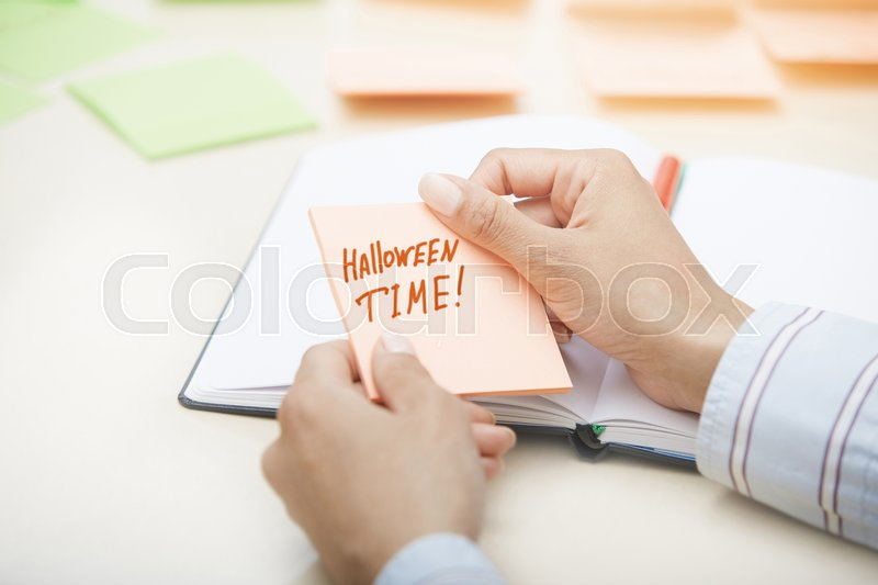Stock image of 'Hands holding sticky note with Halloween Time text'
