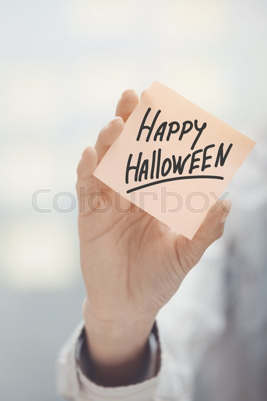 Stock image of 'Woman holding sticky note with Happy Halloween text'
