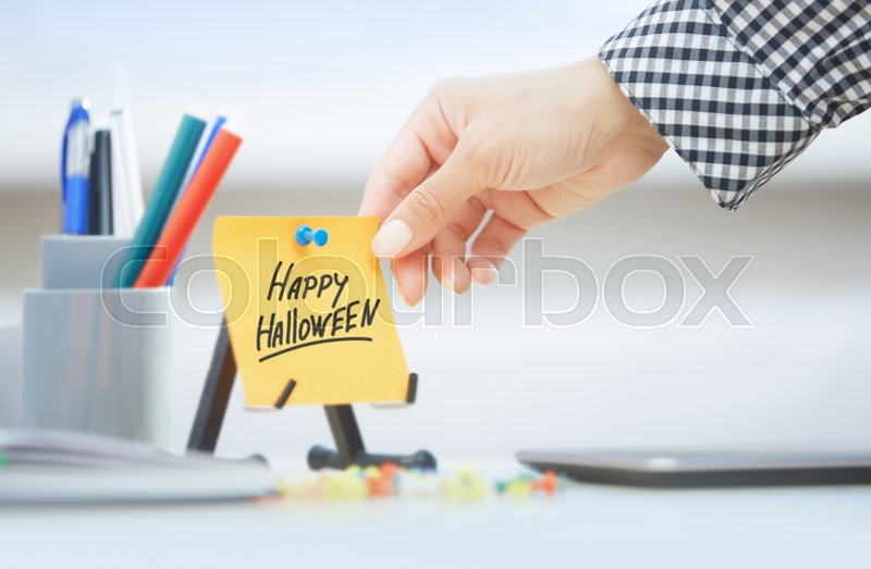 Stock image of 'Hand taking sticky note with Happy Halloween text'