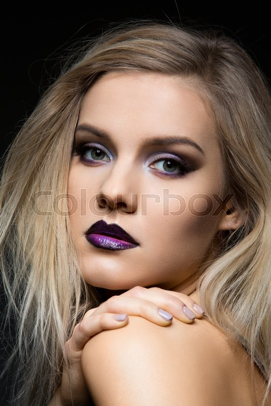 Stock image of 'Beautiful young woman with dark purple eye make-up and lips. Modern fluffy styled blond hair. Studio beauty shot over black background. Copy space.'
