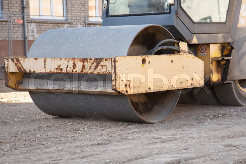 Stock image of 'Road paving equipment working on a street'