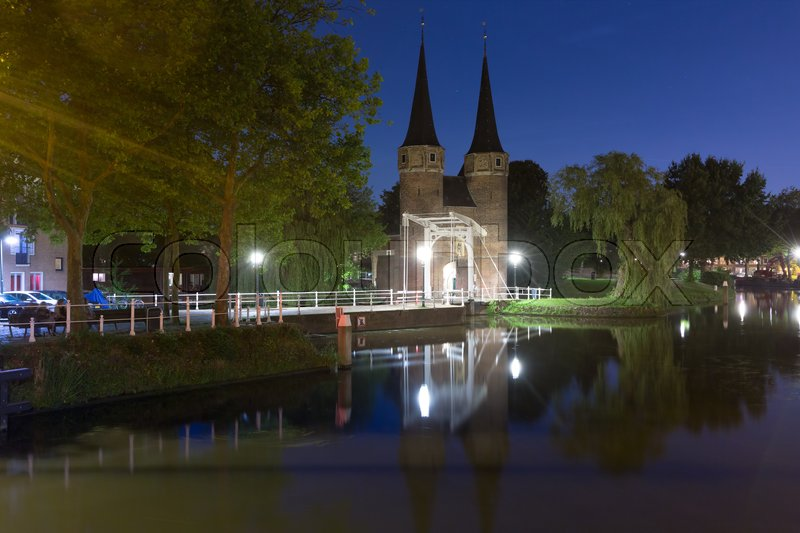 Stock image of 'Eastern Gate, Oostpoort, with the white draw bridge, along Delftse Schie canal at night, Delft, Holland, Netherlands'
