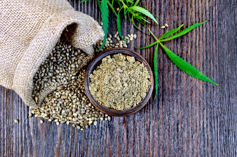 Stock image of 'Hemp flour in a clay bowl, the grain in the bag and on the table, green cannabis leaf on a background of wooden boards on top'