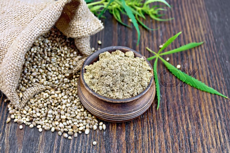 Stock image of 'Hemp flour in a clay bowl, the grain in the bag and on the table, green cannabis leaf on a background of wooden boards'