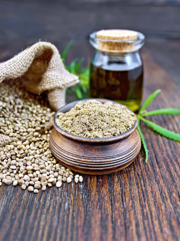 Stock image of 'Hemp flour in a clay bowl, the grain in the bag and on the table, the oil in a glass jar, cannabis leaves on the background of dark wood planks'